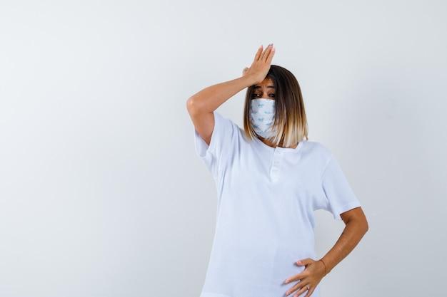 Junge frau, die hand auf stirn in t-shirt, maske und vergesslich aussehend, vorderansicht hält.