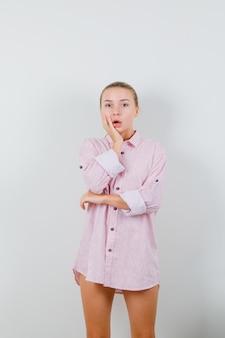 Junge frau, die hand auf wange im rosa hemd hält und überrascht schaut