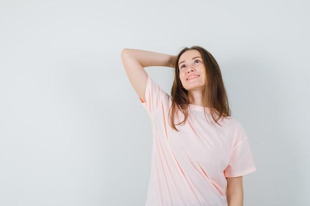 Junge frau, die hand hinter kopf im rosa t-shirt hält und verträumt schaut. vorderansicht.