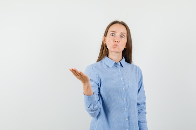 Junge frau, die hand in fragender weise im blauen hemd erhebt und wütend schaut.