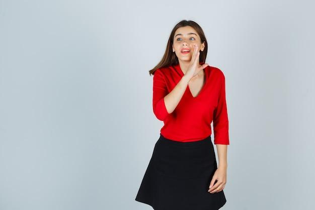Junge frau, die hand nahe mund als erzählendes geheimnis in der roten bluse hält