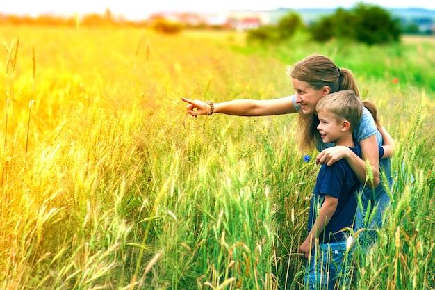 Junge frau, die hand und ihren sohn zeigt, der im weizenfeld steht.