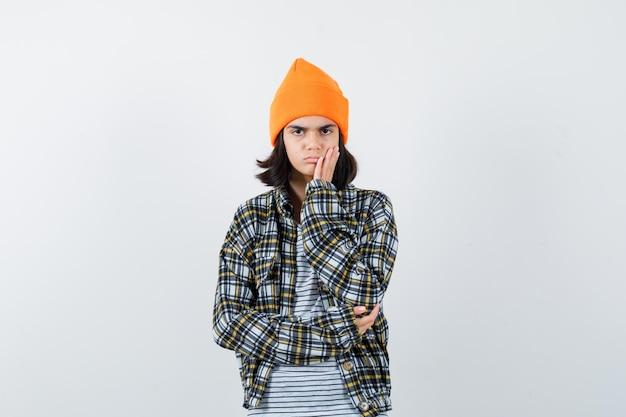 Junge frau, die handfläche auf wange in orangefarbenem, kariertem hemd mit hut hält und nachdenklich aussieht
