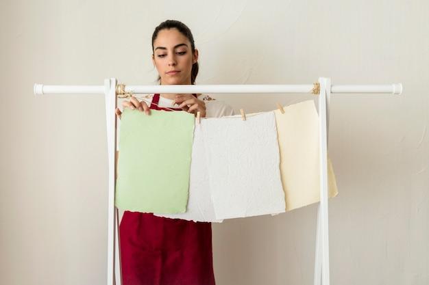 Junge frau, die handgemachte papiere mit wäscheklammer trocknet