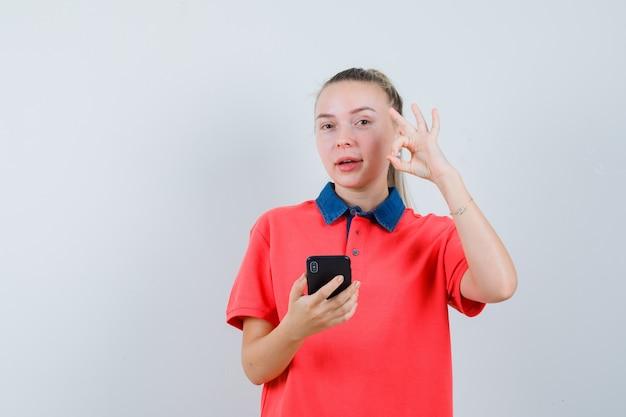 Junge frau, die handy hält, ok geste im t-shirt zeigt und zuversichtlich schaut