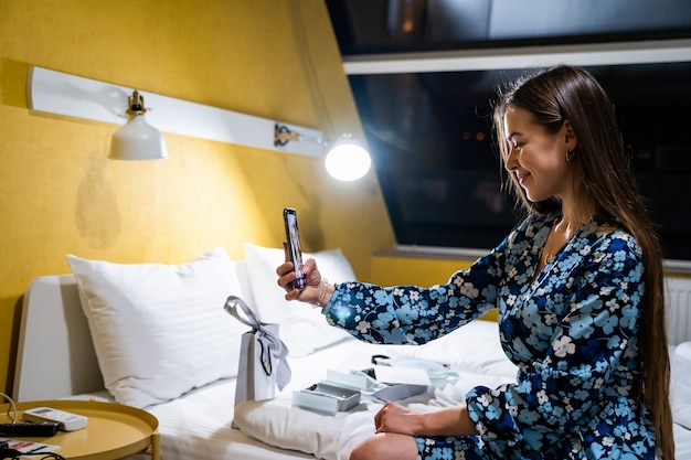 Junge frau, die handy-smartphone benutzt. glückliches lächelndes schönes mädchen auf bett im schlafzimmer nimmt selfie