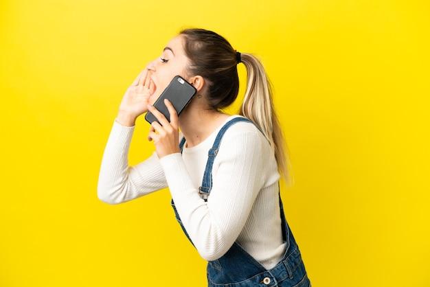 Junge frau, die handy über isoliertem gelbem hintergrund benutzt und mit weit geöffnetem mund zur seite schreit
