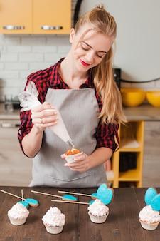 Junge frau, die hausgemachte tasse kuchen in der küche kocht