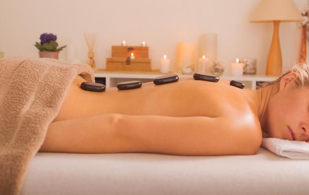 Junge frau, die heißen steinmassage im spa-salon erhält. schönheitsbehandlungskonzept. das mädchen entspannt sich bei spa-behandlungen