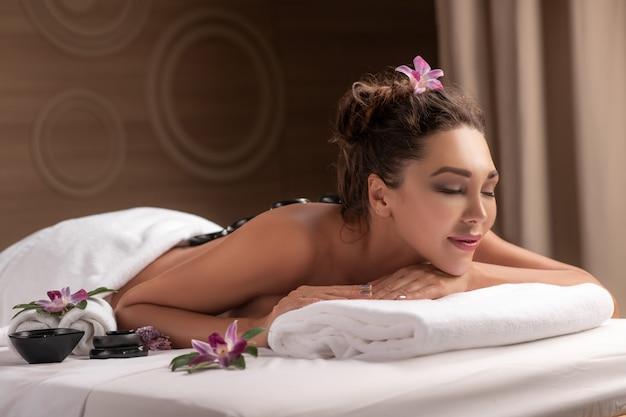 Junge frau, die heißen steinmassage im spa-salon erhält. schönheitsbehandlungskonzept.
