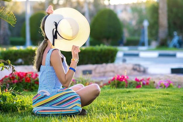 Junge frau, die hellblaues sommerkleid und gelben strohhut trägt, der auf grünem gras entspannt