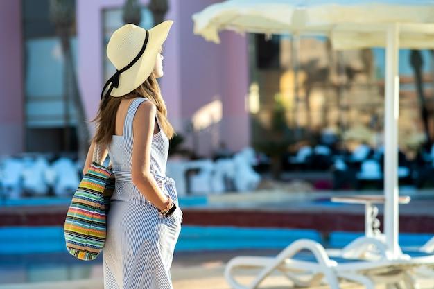 Junge frau, die helles sommerkleid und gelben strohhut trägt, der modische umhängetasche hält, die außerhalb des hotels am sonnigen sommertag steht.