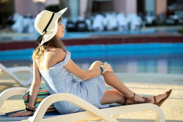 Junge frau, die helles sommerkleid und gelben strohhut trägt, die draußen nahe hotelschwimmbad am sonnigen sommertag sitzen.