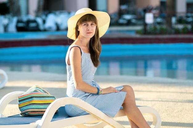Junge frau, die helles sommerkleid und gelben strohhut trägt, sitzt draußen nahe hotelschwimmbad am sonnigen sommertag.