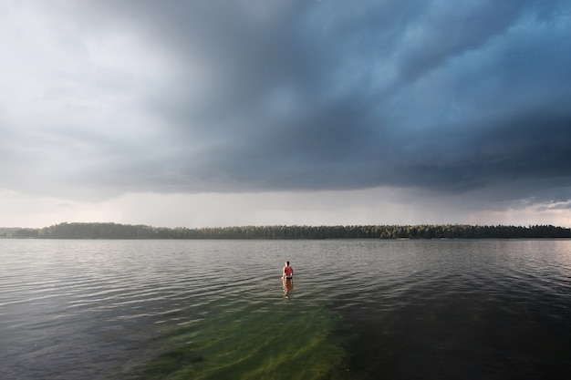 Junge frau, die helles spitzenschwimmen im see schwimmt.