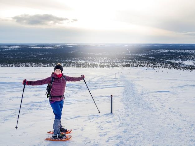 Junge frau, die herrliches winterwetter snowshoeing und genießt