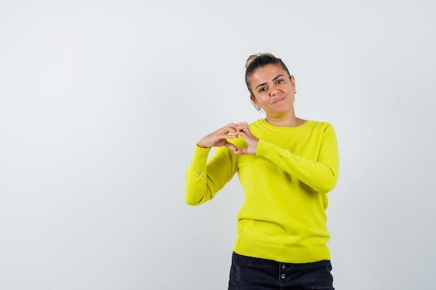 Junge frau, die herzform mit händen in gelbem pullover und schwarzer hose zeigt und glücklich aussieht looking