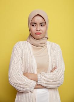 Junge frau, die hijab mit einem ausdruck einsamer verschränkter arme trägt, lokalisiert auf gelbem hintergrund