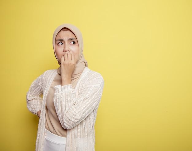 Junge frau, die hijab mit einem erschrockenen ausdruck lokalisiert auf gelbem hintergrund trägt