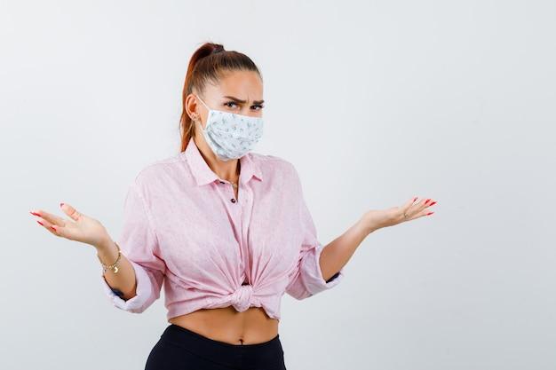 Junge frau, die hilflose geste im hemd, in der hose, in der medizinischen maske zeigt und zögernd schaut. vorderansicht.