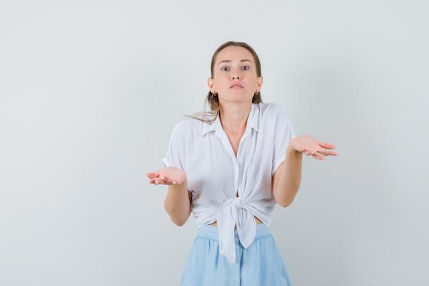 Junge frau, die hilflose geste in bluse und rock zeigt und verwirrt schaut