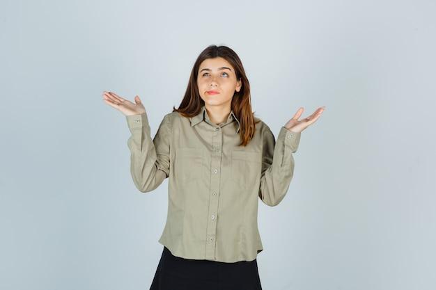 Junge frau, die hilflose geste zeigt, während sie lippen im hemd krümmt