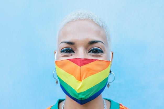 Junge frau, die homosexuell stolzmaske trägt - lgbt rechte, vielfalt, toleranz und geschlechtsidentitätskonzept