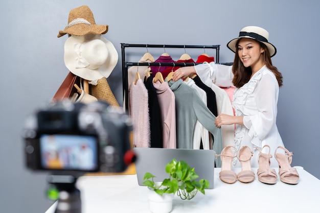 Junge frau, die hut und kleidung online durch kamera-live-streaming, geschäftlichen online-e-commerce zu hause verkauft