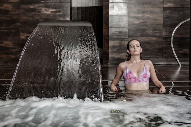 Junge frau, die hydromassage im spa-pool genießt