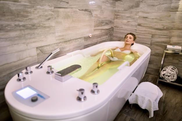 Junge frau, die hydromassage im whirlpoolbad mit grünen lichtern genießt. entspannte frau, die hydromassage im professionellen spa-zentrum erhält
