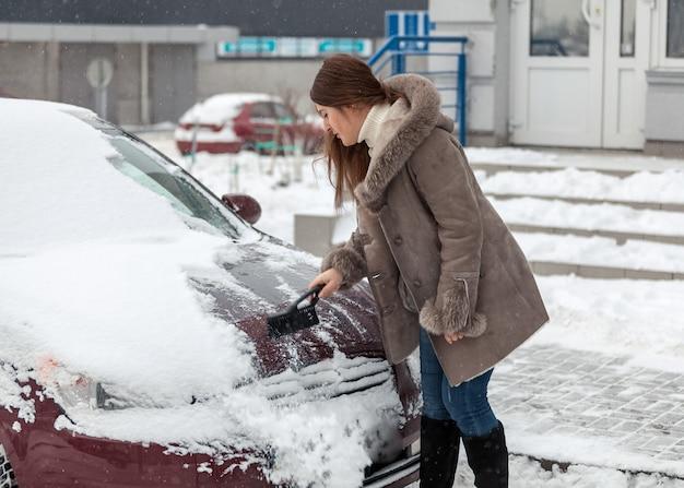 Junge frau, die ihr auto nach schneesturm säubert
