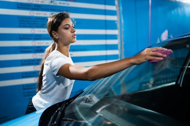 Junge frau, die ihr auto putzt
