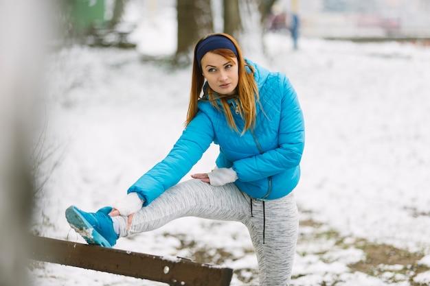 Junge frau, die ihr bein auf schneebedeckter landschaft in der wintersaison ausdehnt