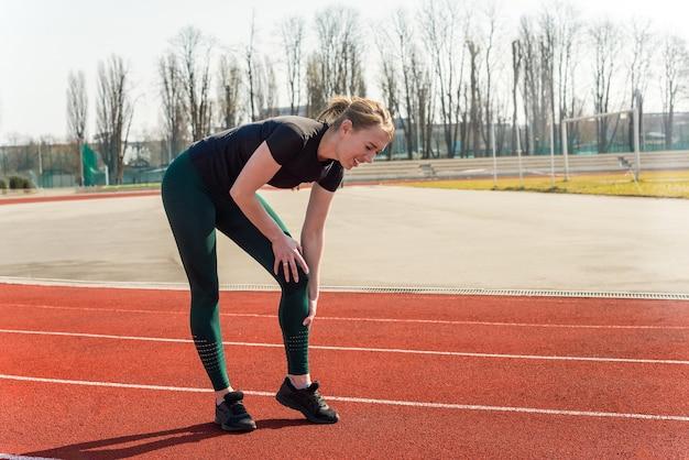 Junge frau, die ihr bein im schmerz am stadion hält. laufende sportverletzungsfraktur des dislozierten gelenks.