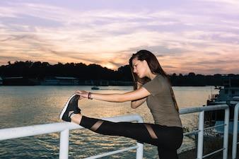 Junge Frau, die ihr Bein nahe Fluss bei Sonnenuntergang ausdehnt