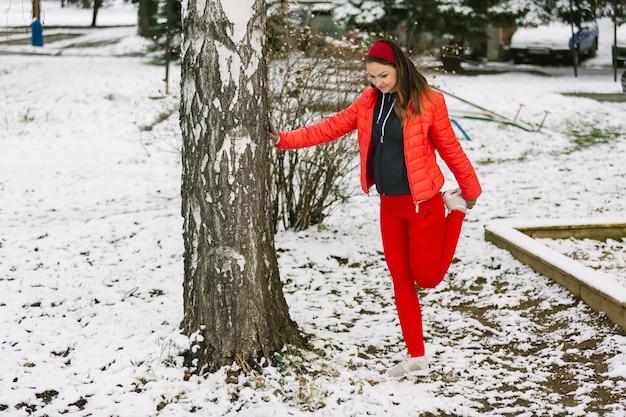 Junge frau, die ihr bein unter dem baum im winter ausdehnt