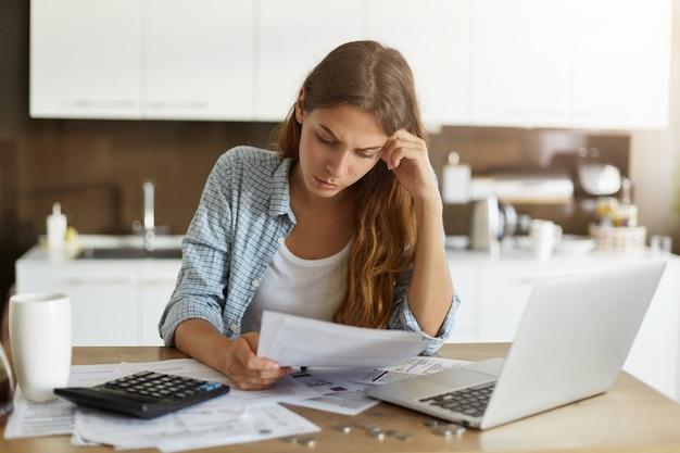 Junge frau, die ihr budget überprüft und steuern tut