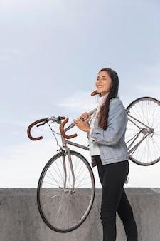 Junge frau, die ihr fahrrad hält