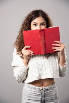 Junge frau, die ihr gesicht mit einem roten buch an einer grauen wand bedeckt. hochwertiges foto