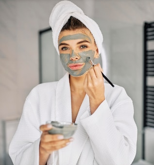 Junge frau, die ihr gesicht mit einer natürlichen maske bedeckt