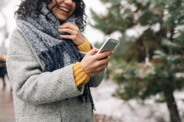 Junge frau, die ihr handy an einem verschneiten winterpark benutzt. nahaufnahme der frau, die nachrichten und sms auf ihrem handy im freien während der kalten wintersaison überprüft. gadget-konzept der menschen.