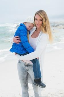 Junge frau, die ihr kleines mädchen am strand trägt