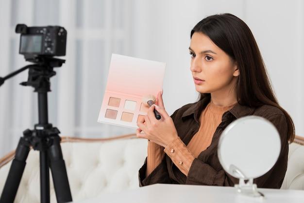 Junge frau, die ihr make-up auf kamera tut