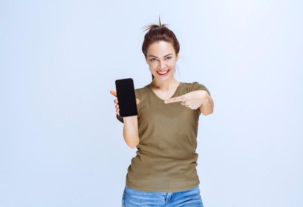 Junge frau, die ihr neues modell des schwarzen smartphones demonstriert