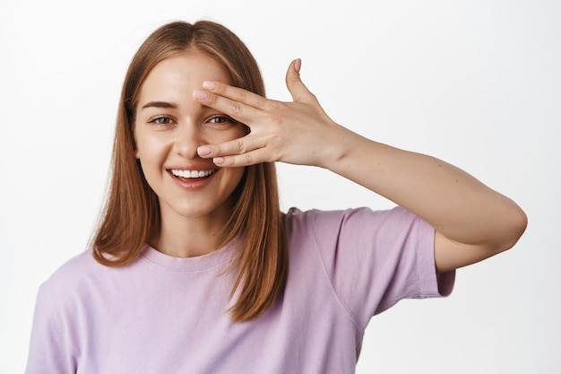 Junge frau, die ihr sauberes gesicht zeigt, gesichtshaut ohne make-up, natürliches weibliches aussehen, offene finger in der nähe des auges und glücklich lächelnd, gegen weiße wand stehend