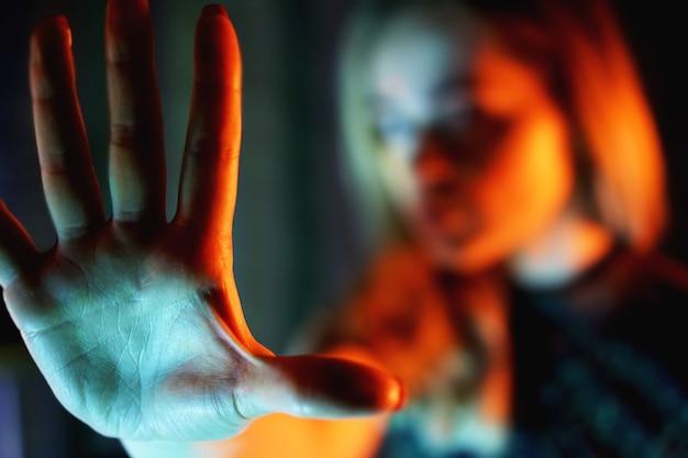 Junge frau, die ihre ablehnung mit nein auf der hand zeigt - neonlichter - verschwommener hintergrund