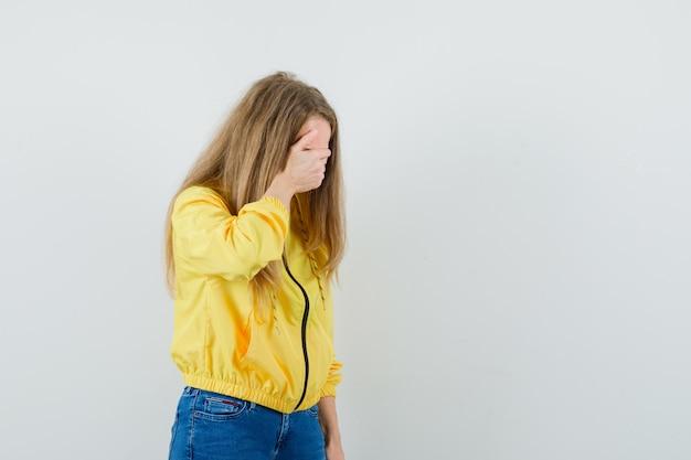 Junge frau, die ihre augen mit der hand in der gelben bomberjacke und in der blauen jeans bedeckt und schüchtern aussieht. vorderansicht.