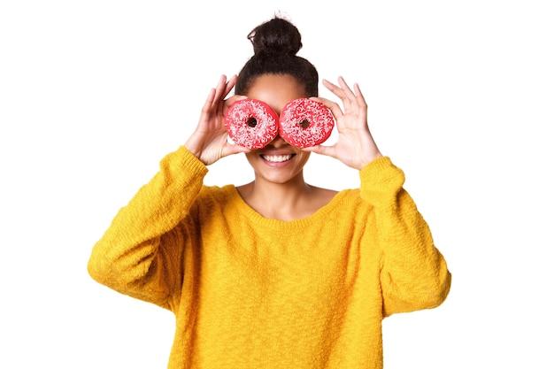 Junge frau, die ihre augen mit donut bedeckt