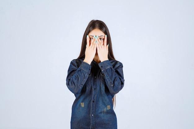 Junge frau, die ihre augen oder einen teil des gesichts schließt und durch ihre finger schaut