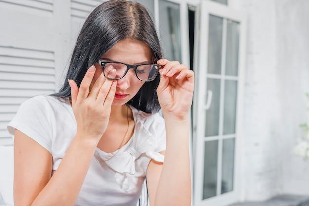 Junge frau, die ihre augen unter den brillen berührt